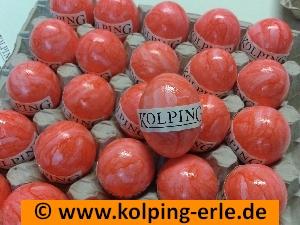 Das Bild zeigt eine Palette mit orangefarbenen Eiern, auf denen der Schriftzug Kolping geklebt wurde