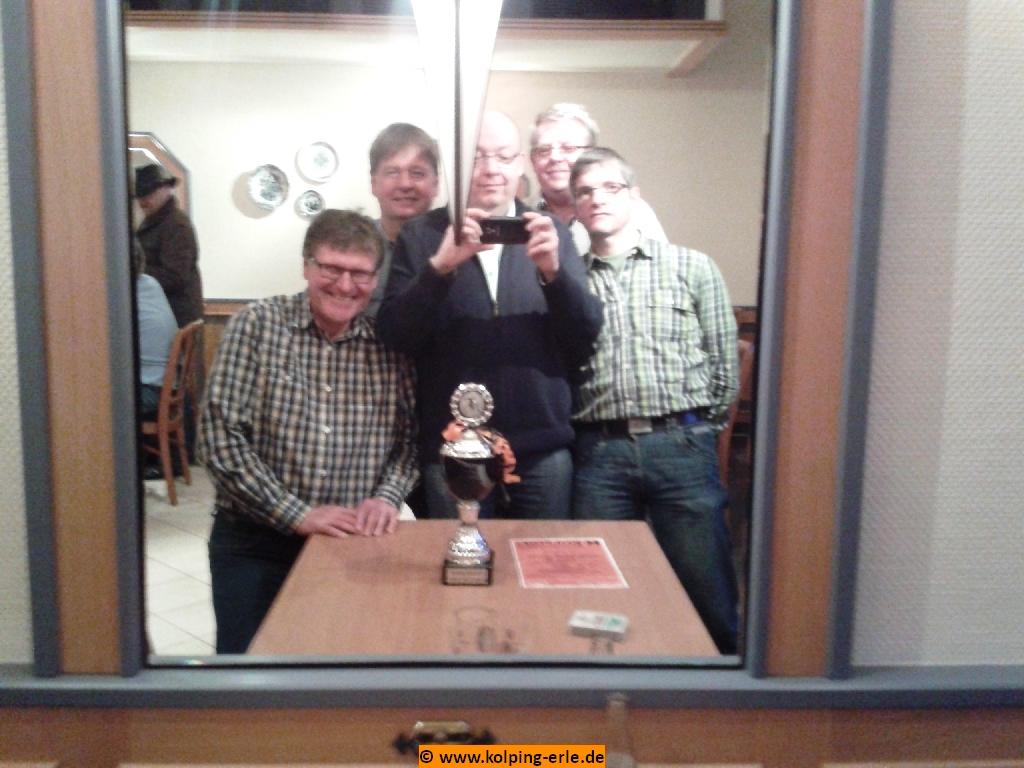 Das Bild zeigt einen Teil der siegreichen Mannschaft mit dem Siegerpokal beim Fotografieren im Spiegel